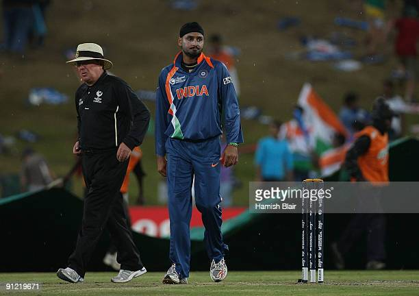 Harbhajan Singh of India and umpire Ian Gould leave the field as rain stops play during the ICC Champions Trophy Group A match between Australia and...