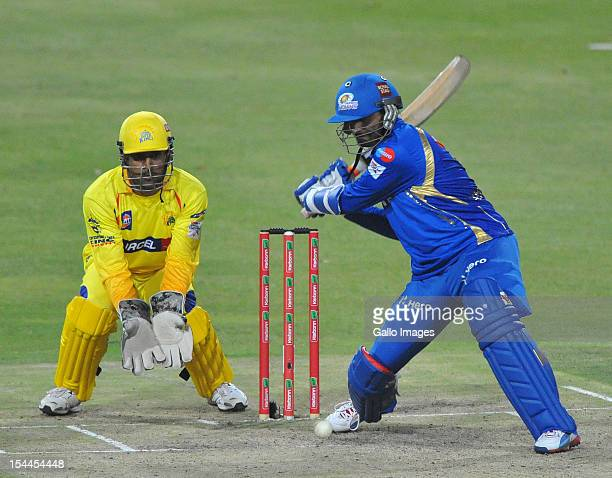 Harbhajan Singh of Mumbai about to hit a boundary with MS Dhoni looking on during the Karbonn Smart CLT20 match between Chennai Super Kings and...