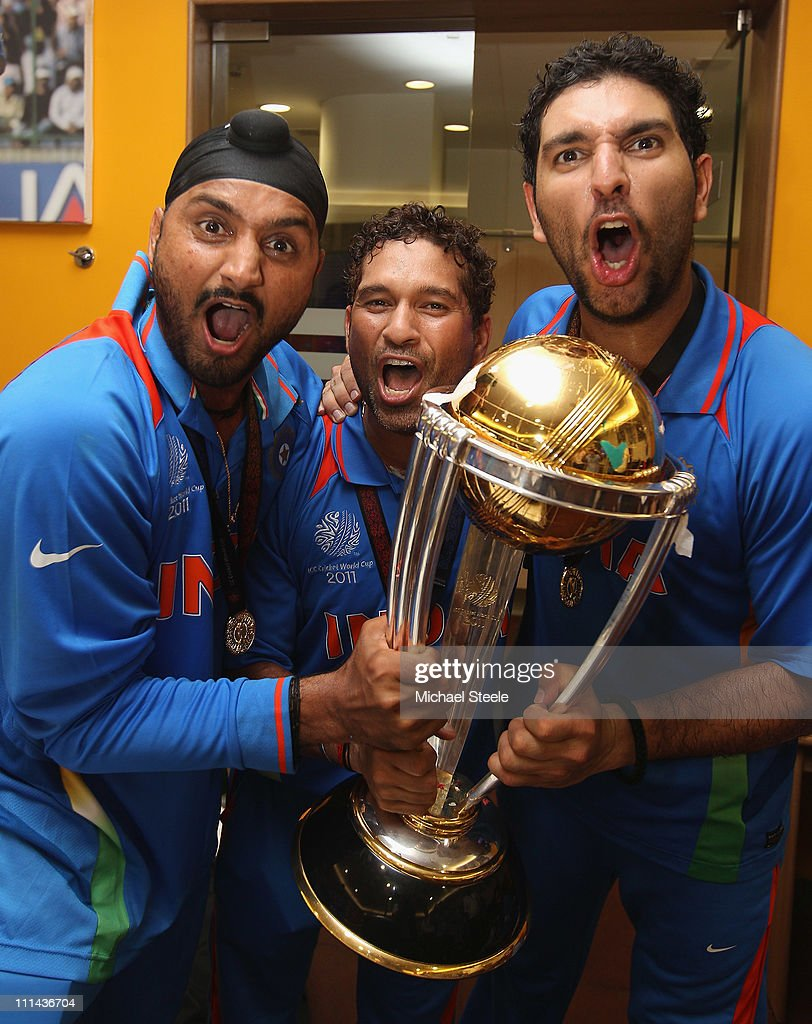 Harbhajan Singh (L),Sachin Tendulkar (C) and Yuvraj Singh (R) with the winners trophy in the players dressing room during the 2011 ICC World Cup Final between India and Sri Lanka at Wankhede Stadium on April 2, 2011 in Mumbai, India.