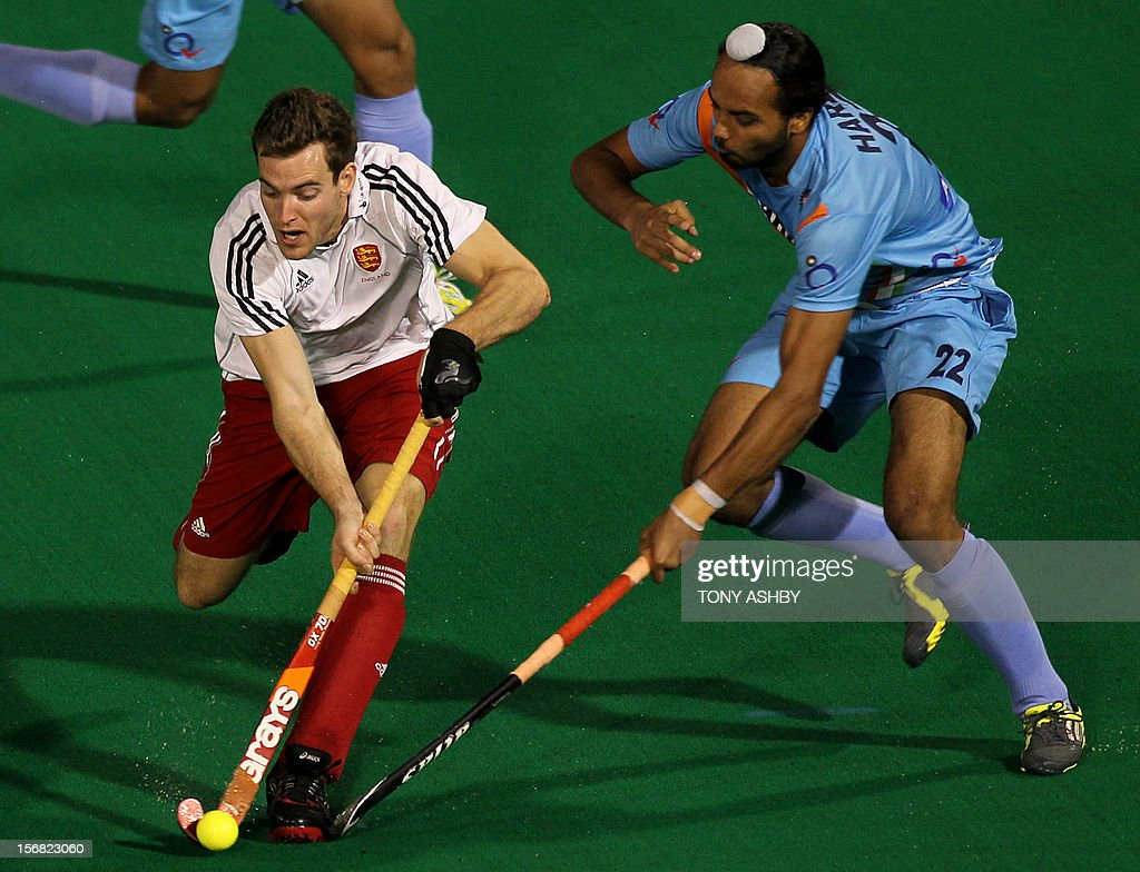 Harbir Singh Sandhu of India (R) challenges Ally Brogdon of England (L) during their men's match at the International Super Series hockey tournament in Perth on November 22, 2012.