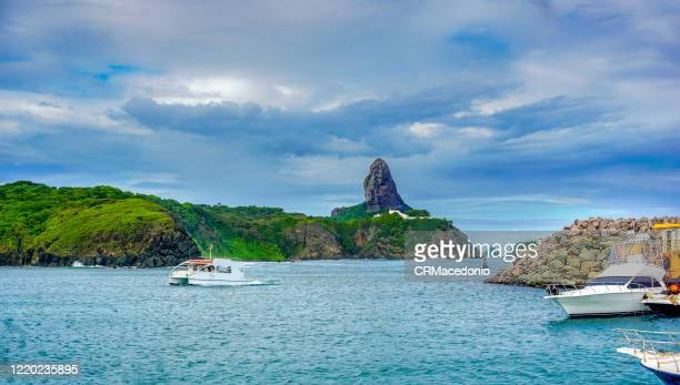 harbor de santo antônio de noronha beach. this is where the boats that supply the island arrive and the starting point for sightseeing. it has a small sandy beach, with calm waters. - crmacedonio - fotografias e filmes do acervo