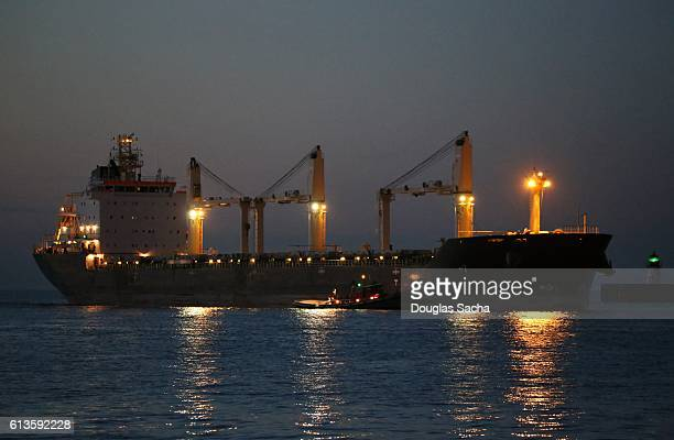 Harbor tug assists a freight ship at night time
