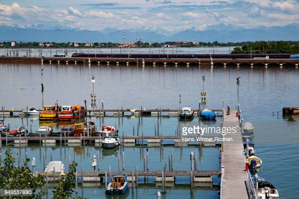 Harbour for recreational crafts, with road and railway embankment, view over the lagoon of Venice, behind the Alps, Tronchetto, Venice, Veneto, Italy