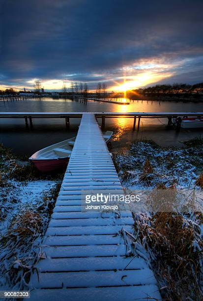 Harbour pontoon in snow and sunset beyond