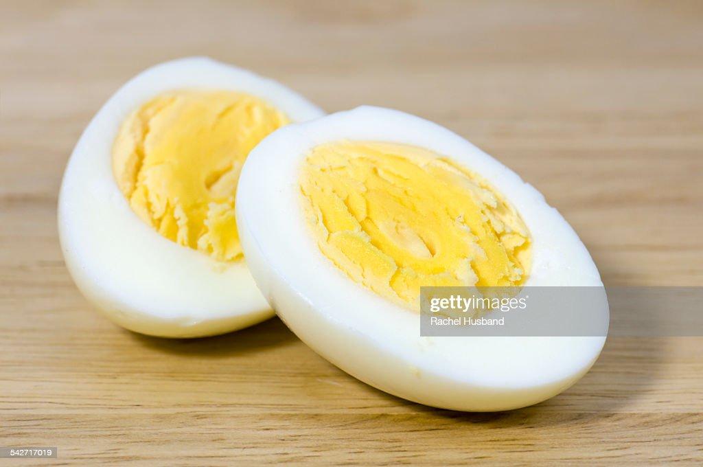 Hard boiled egg cut in half on chopping board : Stock Photo