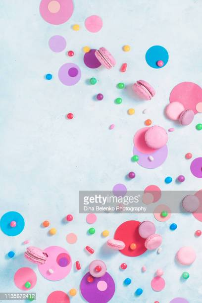 hard candies and macaron cookies. flat lay in pink and purple palette on a white background. party desserts concept - fun background stock pictures, royalty-free photos & images