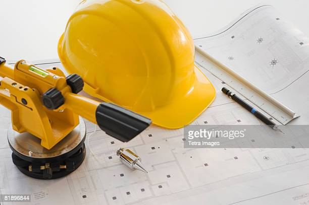 Hard hat and surveying equipment on blueprints