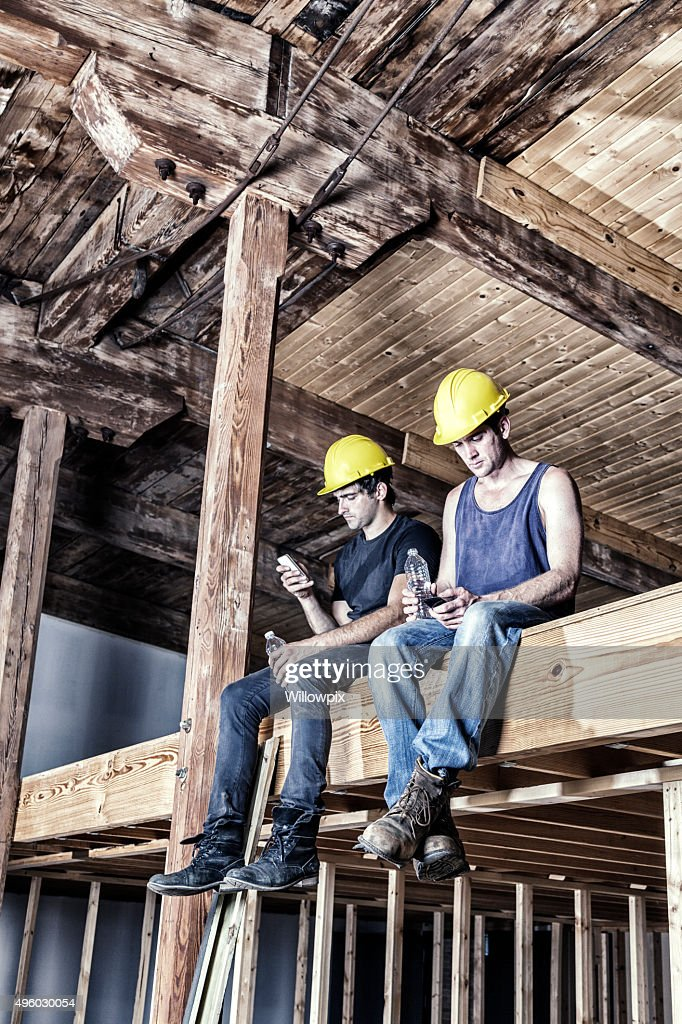 Hard Hat Building Construction Site Workers Resting On Work Break : Stock Photo
