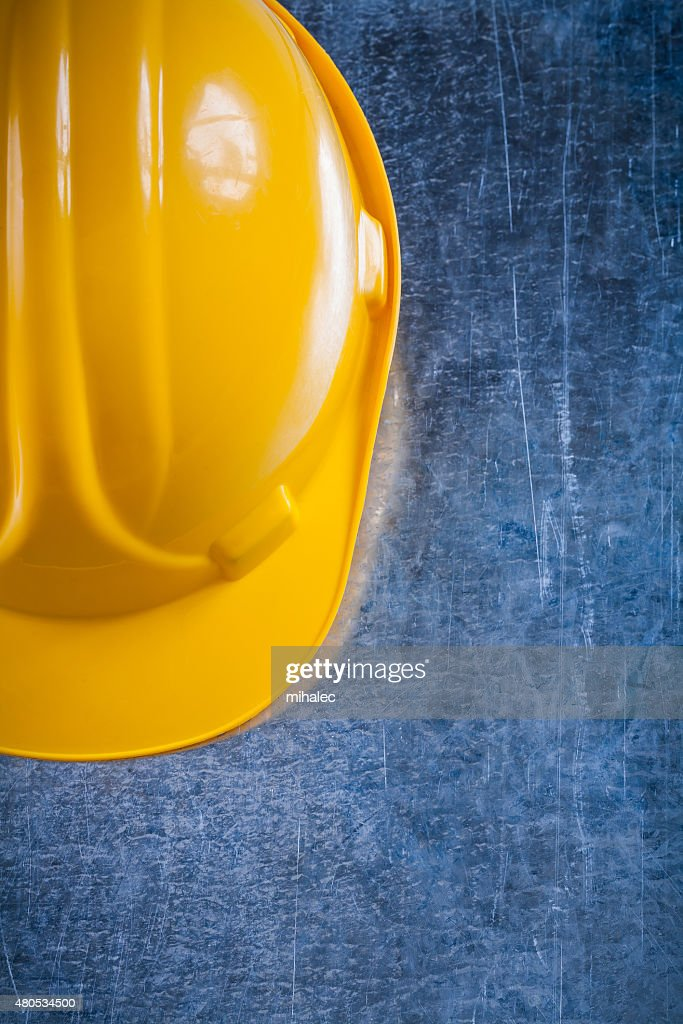 Hard hat on scratched vintage metallic background construction c : Stockfoto