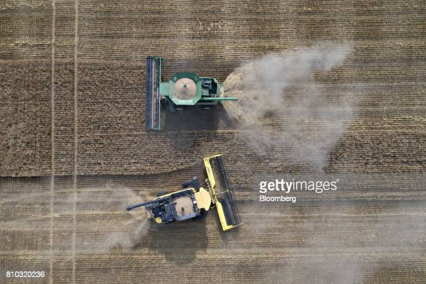 Hard red winter wheat is harvested with a Deere Co John Deere combine harvester top and a CNH Industrial New Holland combine harvester in this aerial...