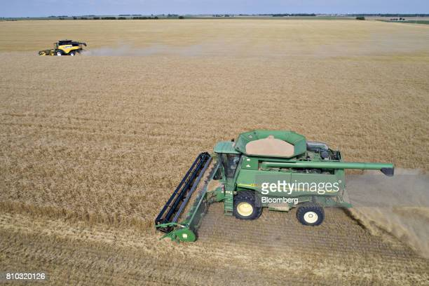 Hard red winter wheat is harvested with Deere Co John Deere right and CNH Industrial New Holland combine harvesters in this aerial photograph taken...