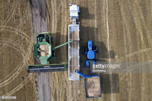 Hard red winter wheat is unloaded from a Deere Co John Deere combine harvester in this aerial photograph taken above Zurich Kansas US on Thursday...