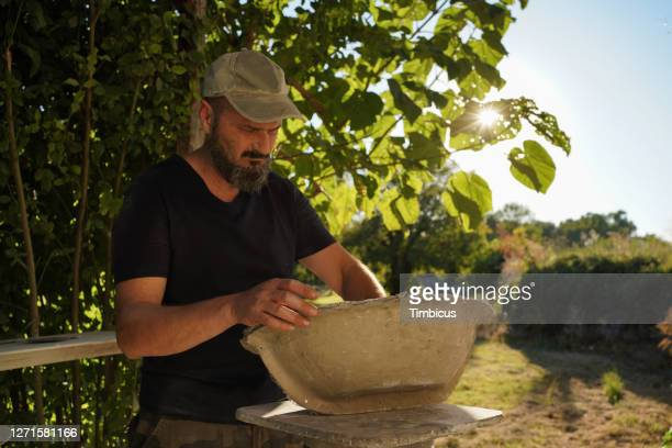 hard working man is putting future wash bowl in mold to inspect is it perfect size in front of his workshop on beautiful sunny day - concentration camp stock pictures, royalty-free photos & images