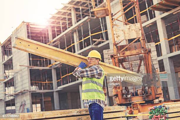 Hard working man on construction platform near crane