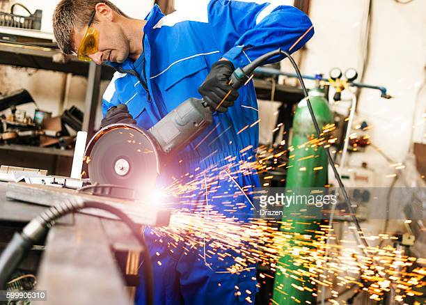 Hard working manual worker in factory, using grinder