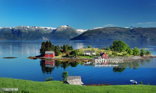 hardangerfjord in south western norway in the summer. a red, norwegian house situated on a small island in the fjord. in the distance the folgefonna glacier. - coastline stock pictures, royalty-free photos & images