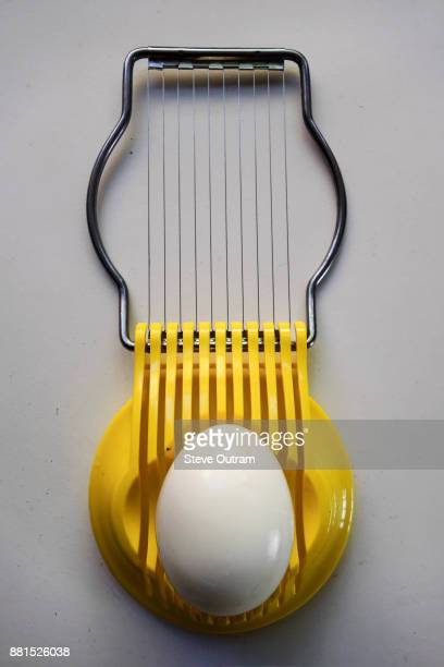 hard-boiled egg in yellow egg slicer - hard boiled eggs stock photos and pictures