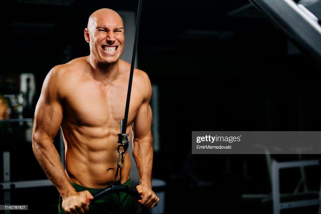 Hardcore workout- bodybuilder exercising using fitness machine : Stock Photo