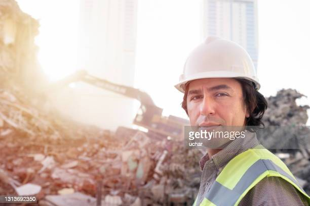 hardhat engineer at the construction site with construction machinery - headwear stock pictures, royalty-free photos & images
