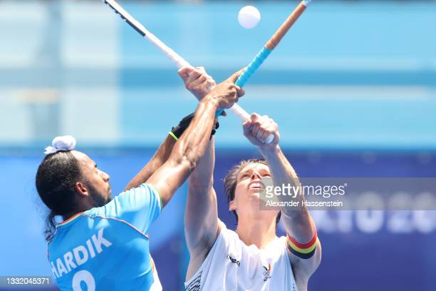 Hardik Singh of Team India and Felix Veronique B. Denayer of Team Belgium battle for a loose ball during the Men's Semifinal match between India and...