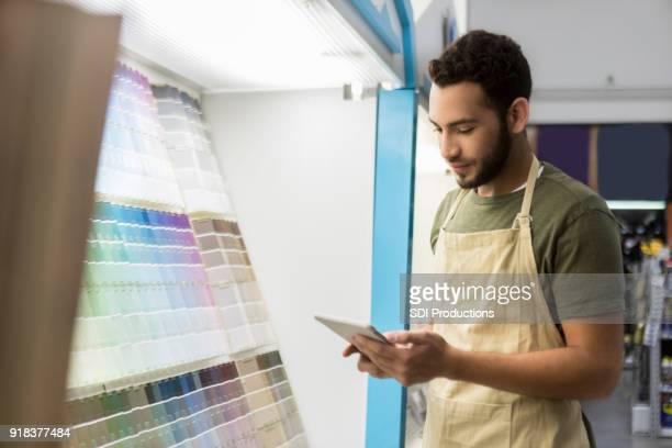 empregado da loja de hardware verifica o inventário no departamento de pintura - independência - fotografias e filmes do acervo