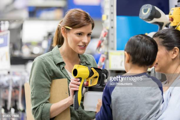 hardware store salesperson shows boy a paint sprayer - construction material stock pictures, royalty-free photos & images