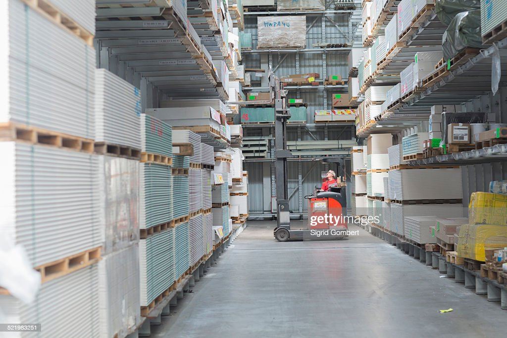Hardware store warehouse worker moving stock in fork lift truck : Stock-Foto