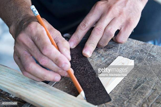 Hardworking carpenter Blue collar Cuban carpenter measuring wooden boards to use on wooden rocking chair