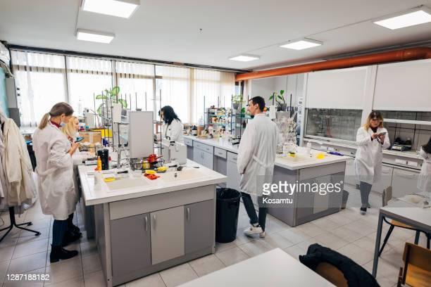 grupo de análisis forenses trabajadores que trabajan en el laboratorio como equipo - grupo mediano de personas fotografías e imágenes de stock