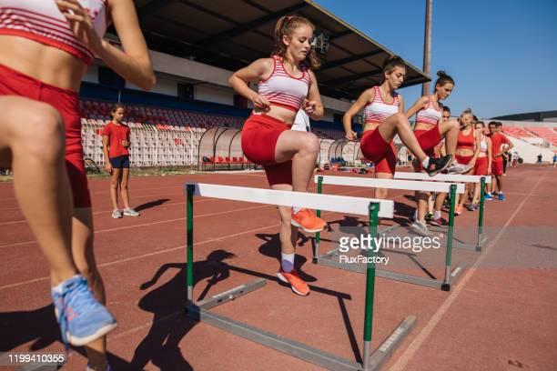 hardworking teenage athletes hurdling on training - warming up stock pictures, royalty-free photos & images