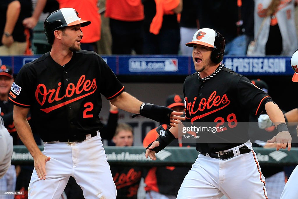 J.J. Hardy #2 celebrates with his teammate Steve Pearce #28 after sliding safe to home plate to score the go ahead run on Delmon Young #27 of the Baltimore Orioles three run RBI double to deep left feild in the eighth inning against Joakim Soria #38 of the Detroit Tigers during Game Two of the American League Division Series at Oriole Park at Camden Yards on October 3, 2014 in Baltimore, Maryland.