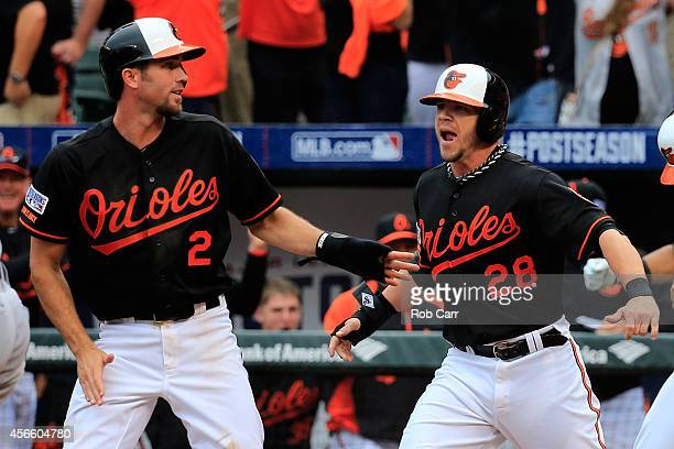 J Hardy celebrates with his teammate Steve Pearce after sliding safe to home plate to score the go ahead run on Delmon Young of the Baltimore Orioles...