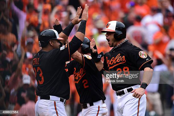 J Hardy celebrates with his teammates Nelson Cruz and Steve Pearce after sliding safe to home plate to score the go ahead run on Delmon Young of the...