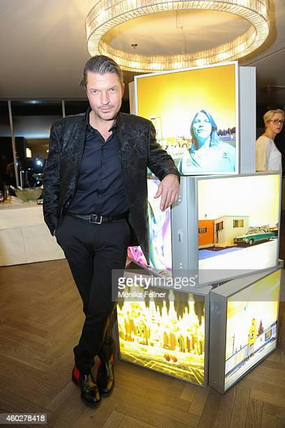 Hardy Krueger Jun poses with one of his pictures at the D'Art by Hardy Krueger Jun Vernissage on December 10 2014 in Vienna Austria