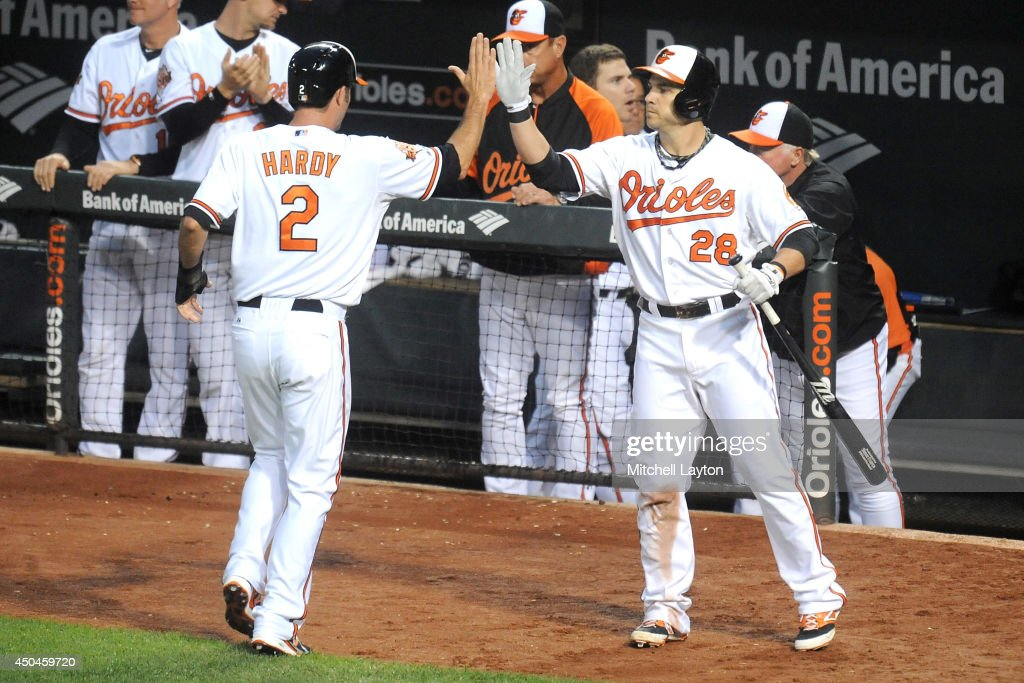 J.J. Hardy #2 of the Baltimore Orioles celebrates scoring the team's fourth run in the fourth inning with Steve Pearce #28 on a Rick Hundley #40 (not pictured) single during a baseball game against the Boston Red Sox on June 11, 2014 at Oriole Park at Camden Yards in Baltimore, Maryland.