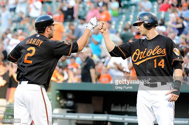 J Hardy of the Baltimore Orioles celebrates with Nolan Reimold after hitting a home run in the first inning against the Detroit Tigers at Oriole Park...