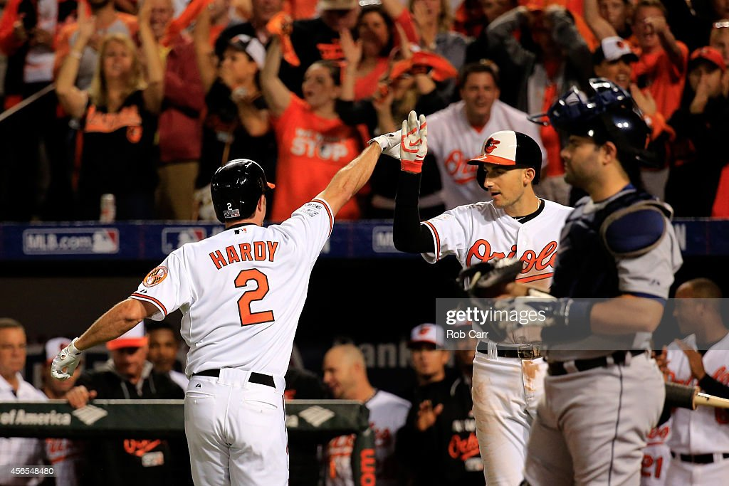 J.J. Hardy #2 of the Baltimore Orioles celebrates with teammate Ryan Flaherty #3 after hitting a solo home run in the seventh inning against Max Scherzer #37 of the Detroit Tigers during Game One of the American League Division Series at Oriole Park at Camden Yards on October 2, 2014 in Baltimore, Maryland.