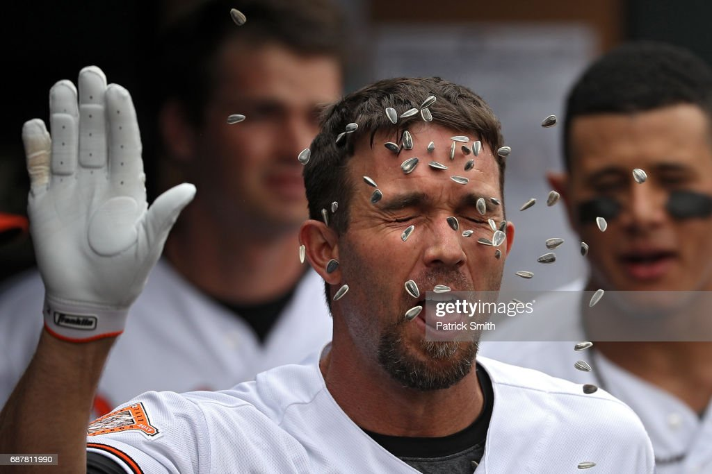 J.J. Hardy #2 of the Baltimore Orioles has sunflower seeds thrown on him as he celebrates in the dugout with teammates after hitting a home run against the Minnesota Twins during the third inning at Oriole Park at Camden Yards on May 24, 2017 in Baltimore, Maryland.