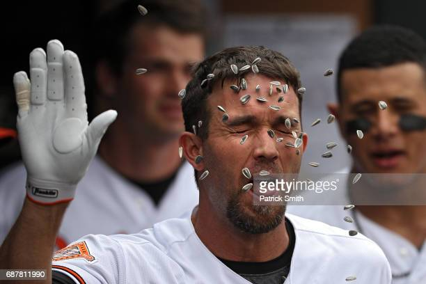 J Hardy of the Baltimore Orioles has sunflower seeds thrown on him as he celebrates in the dugout with teammates after hitting a home run against the...