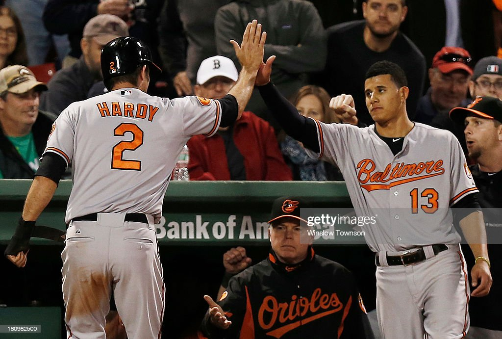 J.J. Hardy #2 of the Baltimore Orioles is congratulated by Manny Machado #13 of the Baltimore Orioles after scoring during the twelfth inning as manager Buck Showalter #26 of the Baltimore Orioles looks on at Fenway Park on September 18, 2013 in Boston, Massachusetts.