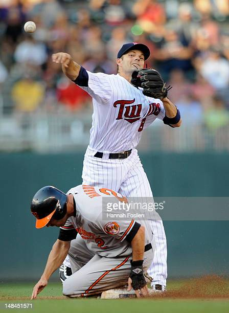 J Hardy of the Baltimore Orioles is out at second base as Jamey Carroll of the Minnesota Twins turns a double play during the first inning on July 16...
