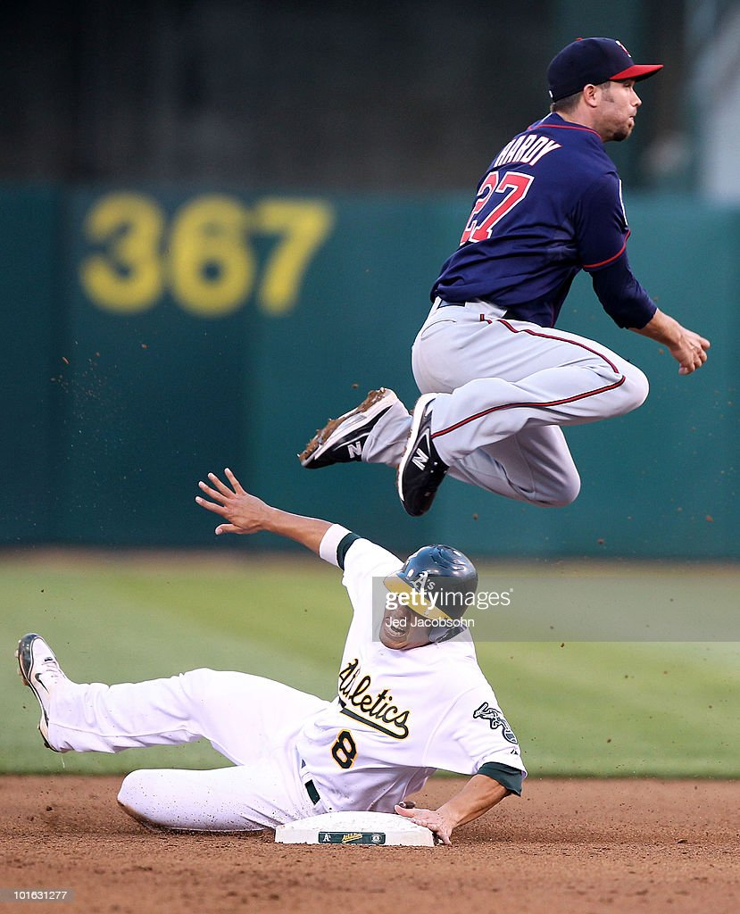 J.J. Hardy #27 of the Minnesota Twins leaps over Kurt Suzuki #8 of the Oakland Athletics on a double play hit by Jack Cust in the fourth inning during an MLB game at the Oakland-Alameda County Coliseum on June 4, 2010 in Oakland, California.