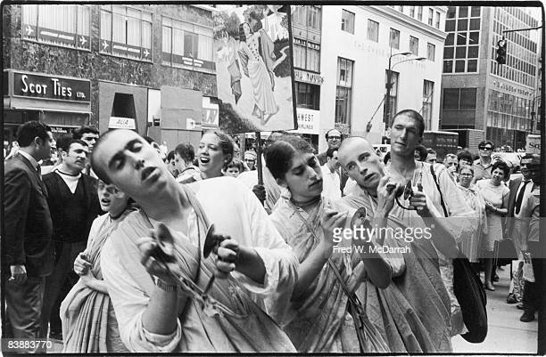 Hare Krishna devotees perform with finger cymbals on the sidewalk of Fifth Avenue New York New York August 2 1969