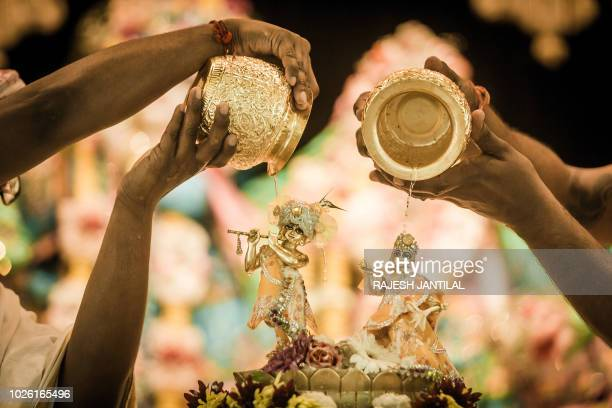 A Hare Krishna priest performs the Abhishekam by pouring milk on the deity of Lord Krishna and Mother Radha Rani during the celebrations of Krishna...
