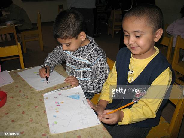 Hareth Muthana and his friend draw together in their class at Mama Ayser Elementary School Many children including Hareth depict images of war in...