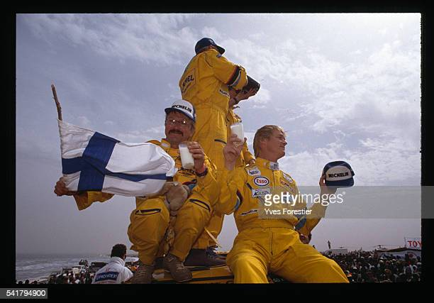 Hari Vatanen and his team celebrate their victory in the car category of the 1990 Paris Dakar Rally by waving a Finnish flag