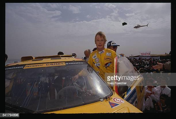 Hari Vatanen next to his Peugeot celebrates his victory in the car category of the 1990 Paris Dakar Rally in Dakar