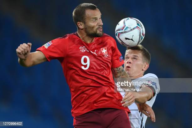 Haris Seferovic of Switzerland is challenged by Matthias Ginter of Germany during the UEFA Nations League group stage match between Switzerland and...