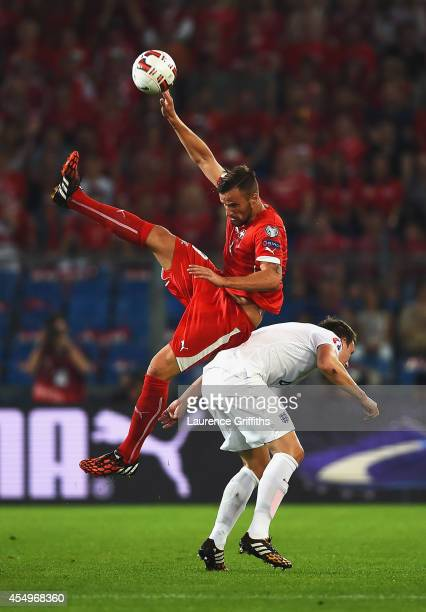 Haris Seferovic of Switzerland jumps over Phil Jones of England during the UEFA EURO 2016 Group E qualifying match between Switzerland and England at...