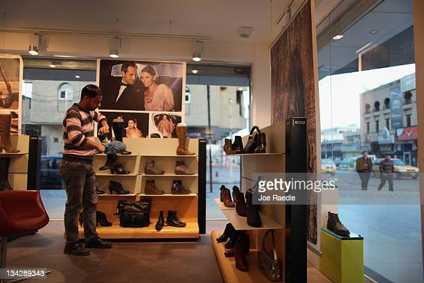 Harith Mohmed dusts off shoes on display in a shoe store on November 30 2011 in Baghdad Iraq Iraq is transitioning as the US military continues its...